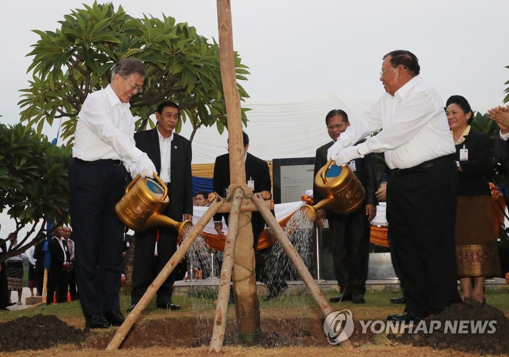 South Korean President Moon Jae-in (L) and his Laotian counterpart, Bounnhang Vorachith, water a tree they planted together on the bank of the Mekong River in Vientiane on Sept. 5, 2019. (Yonhap)