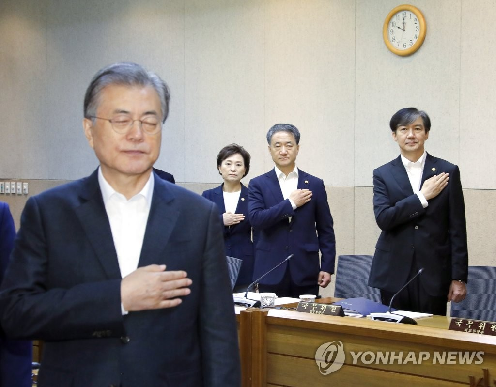 In this file photo, dated Sept. 10, 2019, President Moon Jae-in (L) salutes to South Korea's national flag during a Cabinet meeting, attended by Justice Minister Cho Kuk (R), at the Korea Institute of Science and Technology in Seoul. (Yonhap)