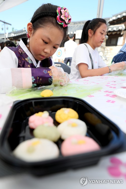 Girl concentrates on making rice cake