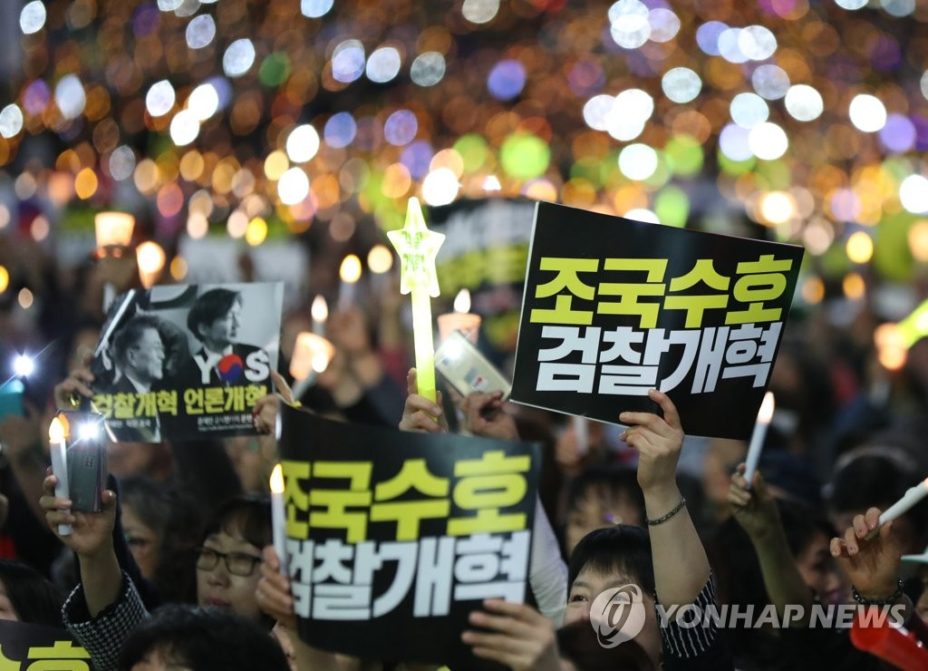 "Supporters of Justice Minister Cho Kuk hold up signs reading ""Protect Cho Kuk"" and ""Reform Prosecution"" during a candlelight vigil held in front of the headquarters of the Supreme Prosecutors Office in southern Seoul on Oct. 12, 2019. (Yonhap)"