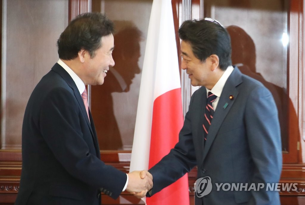 This file photo, taken Sept. 11, 2018, shows South Korean Prime Minister Lee Nak-yon (L) shaking hands with Japanese Prime Minister Shinzo Abe at talks in Vladivostok on the sidelines of an economic forum. (Yonhap)