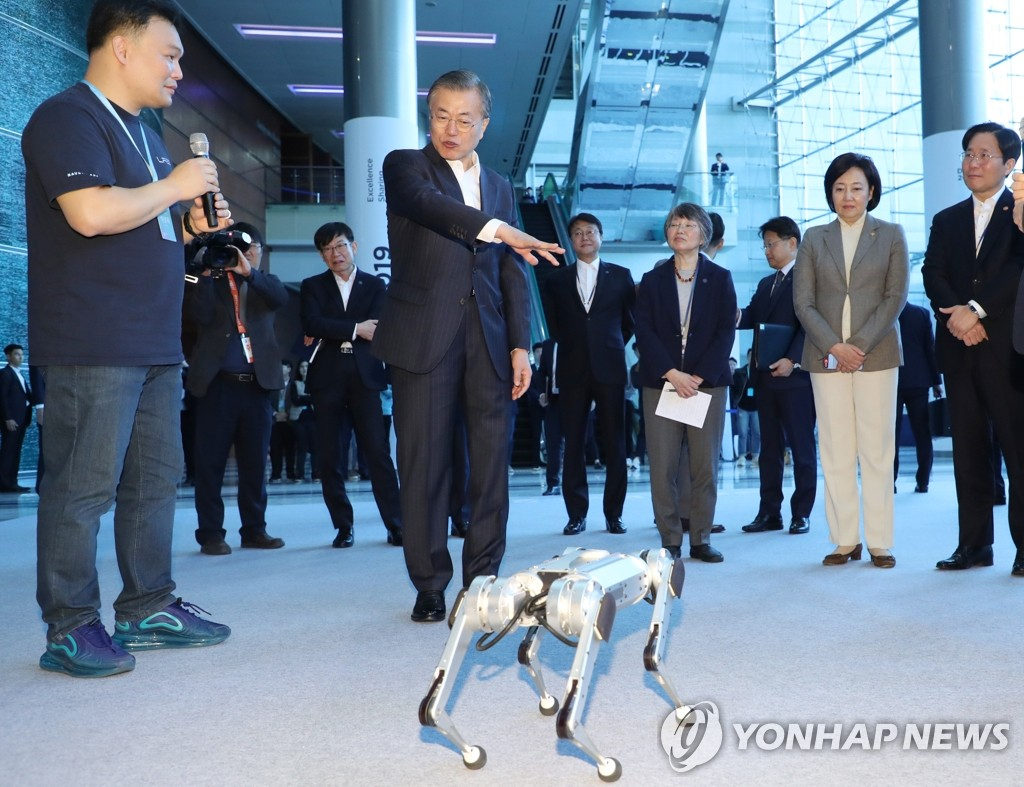 "President Moon Jae-in is briefed on a four-legged ""mini-cheetah"" robot on a visit to the DEVIEW 2019 conference held at the COEX convention center in Seoul on Oct. 28, 2019. (Yonhap)"