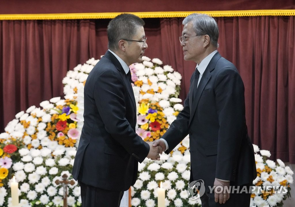 President Moon Jae-in (R) greets Hwang Kyo-ahn, head of the main opposition Liberty Korea Party, who visited Namcheon Catholic Cathedral in Busan on Oct. 30, 2019, to mourn the death of Moon's mother, in this photo provided by Cheong Wa Dae. (PHOTO NOT FOR SALE) (Yonhap)