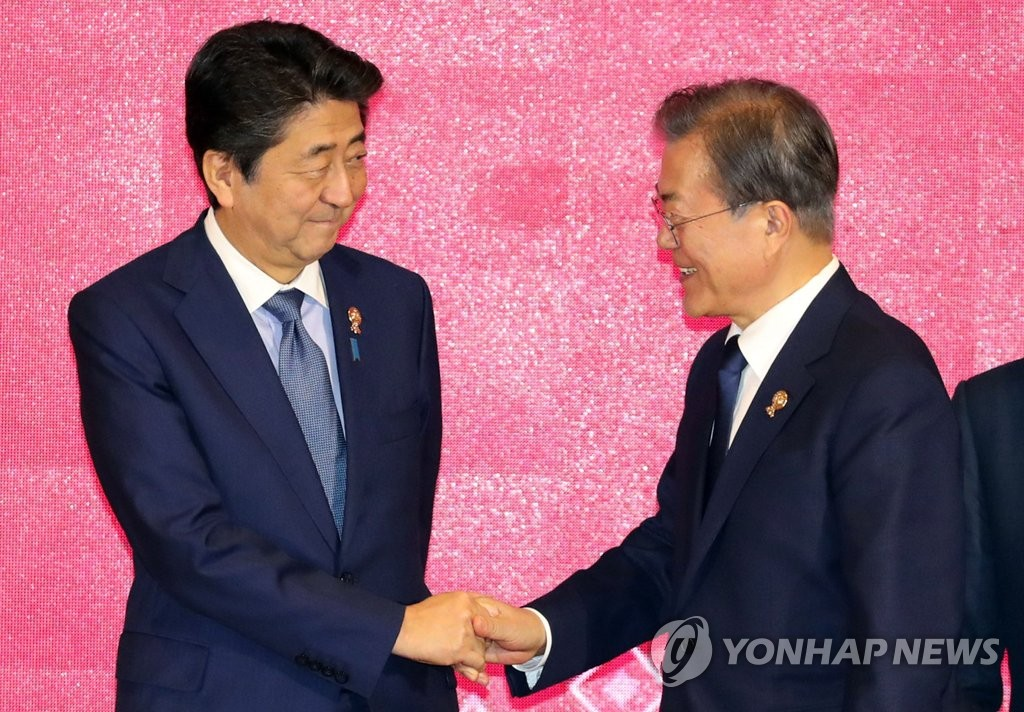 South Korean President Moon Jae-in (R) shakes hands with Japanese Prime Minister Shinzo Abe at the Regional Comprehensive Economic Partnership (RCEP) summit in Bangkok on Nov. 4, 2019. (Yonhap)