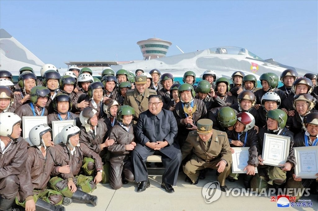 North Korean leader Kim Jong-un (C) smiles during a photo session with pilots in this photo provided by the North's official Korean Central News Agency (KCNA) on Nov. 16, 2019. The KCNA reported that Kim watched the military air show at Wonsan Kalma Airport on the North's east coast. (For Use Only in the Republic of Korea. No Redistribution) (Yonhap)