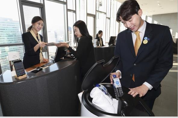 Models of KT Corp. introduce N bot, an artificial intelligence hotel robot, designed to serve guests at Novotel Ambassador Seoul Dongdaemun Hotels & Residences in Seoul, on Dec. 2, 2019, in this photo provided by the telecom operator. (PHOTO NOT FOR SALE) (Yonhap)