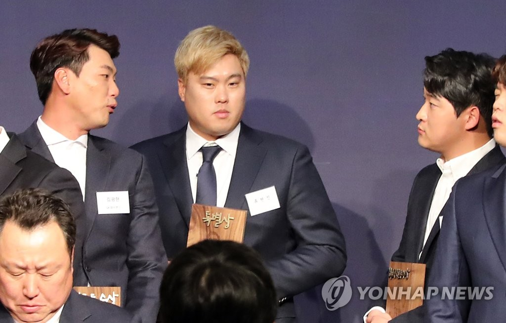 South Korean pitchers Kim Kwang-hyun (L) and Ryu Hyun-jin (C) chat during a baseball awards ceremony in Seoul on Dec. 4, 2019. (Yonhap)