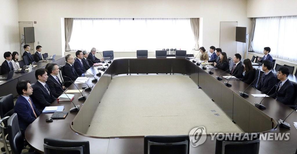 会議室に座った韓国側代表団(右)と日本側代表団=16日、東京(共同通信=聯合ニュース)