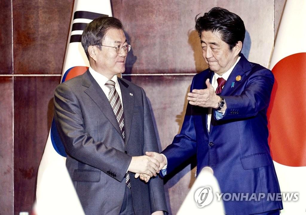 握手を交わす文大統領(左)と安倍首相=24日、成都(聯合ニュース)