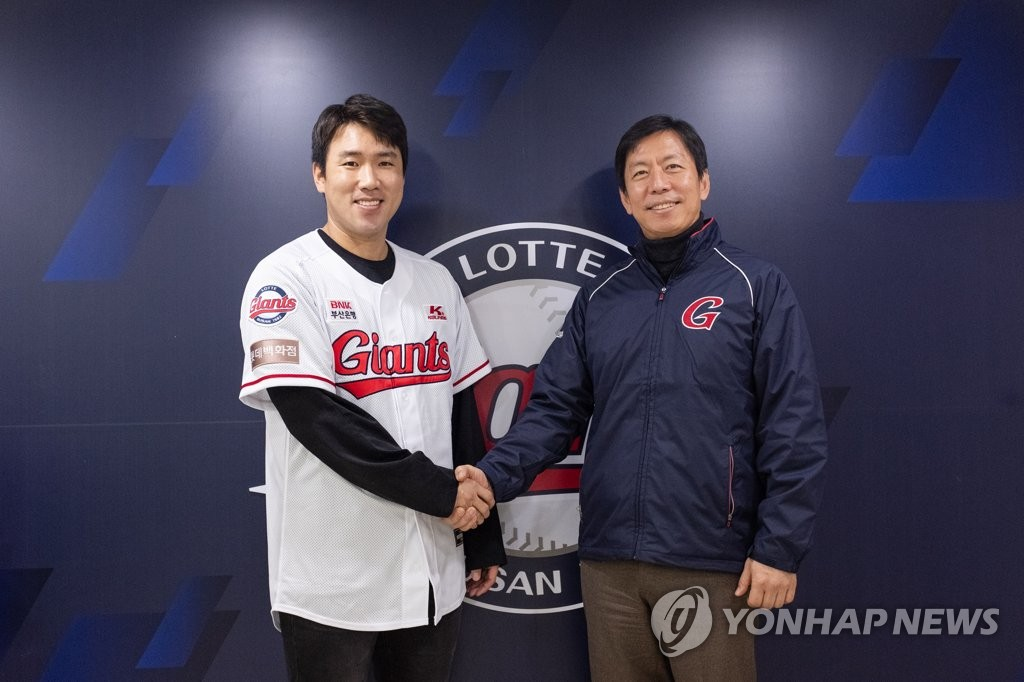 In this photo provided by the Lotte Giants on Jan. 8, 2020, Jeon Jun-woo (L), outfielder for the Giants, shakes hands with team president Lee Seok-hwan after signing a four-year contract in free agency to stay with the Korea Baseball Organization club. (PHOTO NOT FOR SALE) (Yonhap)