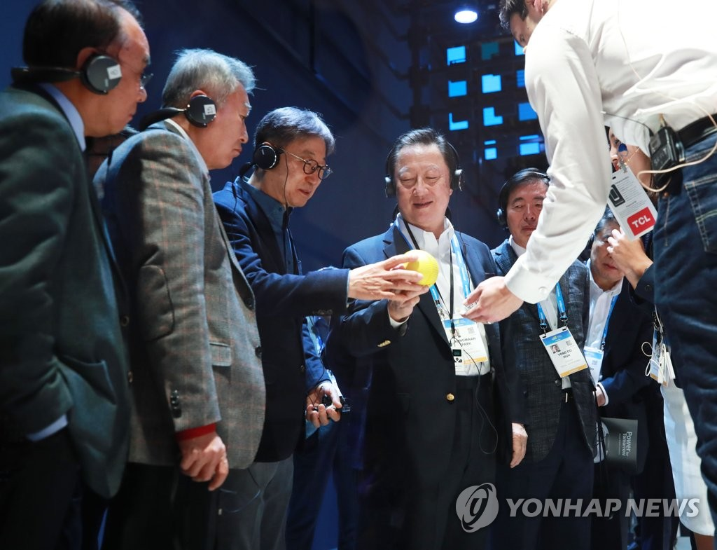 Park Yong-maan (R), chief of the Korea Chamber of Commerce and Industry (KCCI), inspects Samsung Electronics Co.'s rolling bot Ballie with Samsung Electronics Vice Chairman Yoo Boo-keun and other guests at Samsung's Consumer Electronics Show booth in Las Vegas, Nevada. (Yonhap)