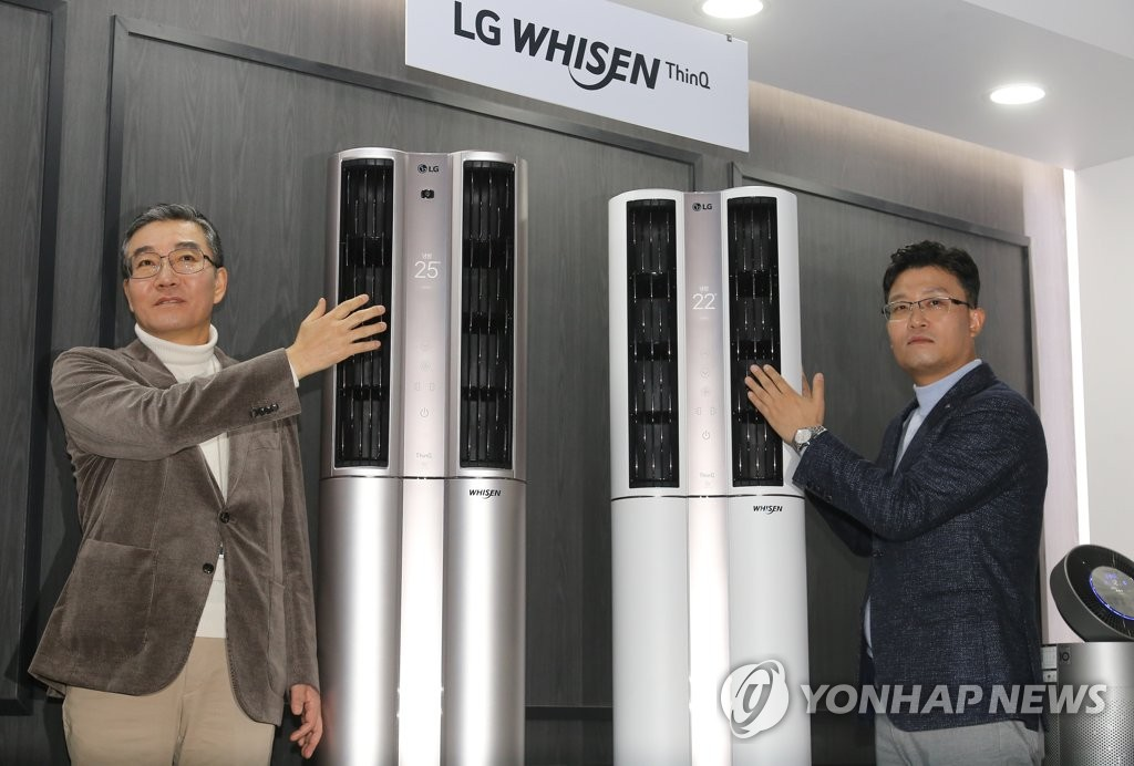 LG Electronics Inc.'s air solution business chief Lee Kam-gyu (L) and the company's B2B marketing chief Yim Jeong-soo pose for a photo with LG's new air conditioners at its product launching event in Seoul on Jan. 16, 2020. (Yonhap)