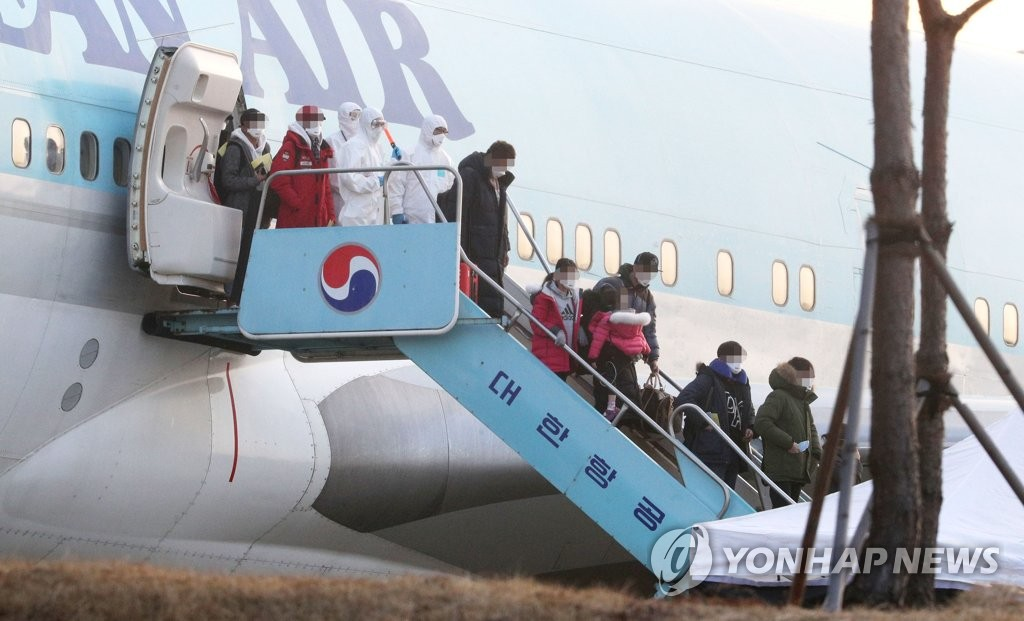South Korean evacuees from the coronavirus-stricken Chinese city of Wuhan debark a chartered Korean Air plane after arriving at Gimpo International Airport in western Seoul on Jan. 31, 2020. (Yonhap)