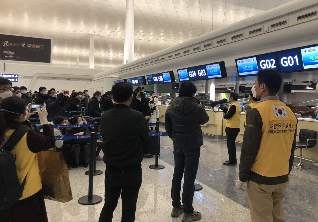 Officials from South Korea's consulate general based in the Chinese city of Wuhan in yellow jackets help South Korean residents board a chartered flight home at Wuhan Tianhe International Airport on Jan. 31, 2020, in this photo provided by a Yonhap reader. (PHOTO NOT FOR SALE) (Yonhap)