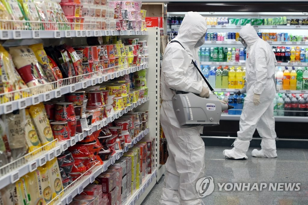 A decontamination team wearing protective gear disinfects a store in Naju, 355 kilometers south of Seoul, on Feb. 6, 2020. (Yonhap)
