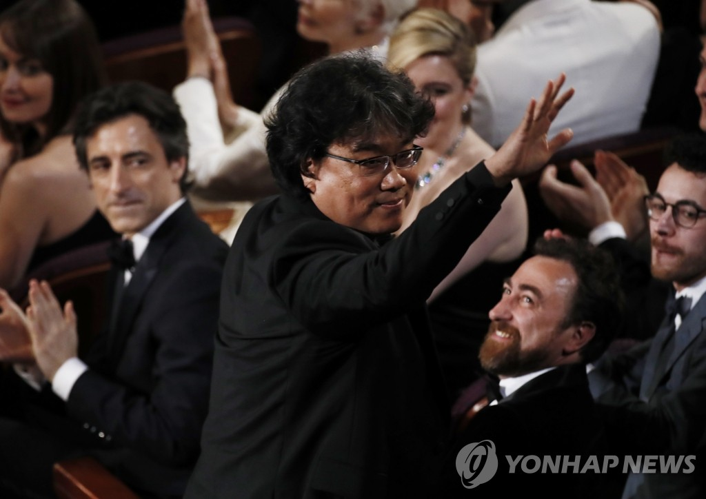 "South Korean director Bong Joon-ho stands up to accept the best original screenplay award for ""Parasite"" during the 92nd Oscars at the Dolby Theatre in Los Angeles on Feb. 9, 2020, in this photo released by Europe's news photo agency, EPA. (Yonhap)"