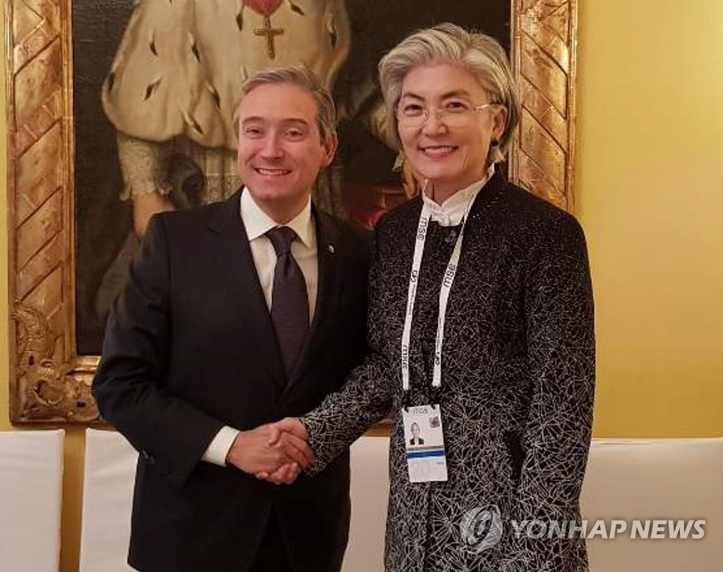 South Korean Foreign Minister Kang Kyung-wha (R) and her Canadian counterpart Francois-Philippe Champagne shake hands ahead of their bilateral meeting held on the sidelines of a security forum in Munich on Feb. 14, 2020. (Yonhap)