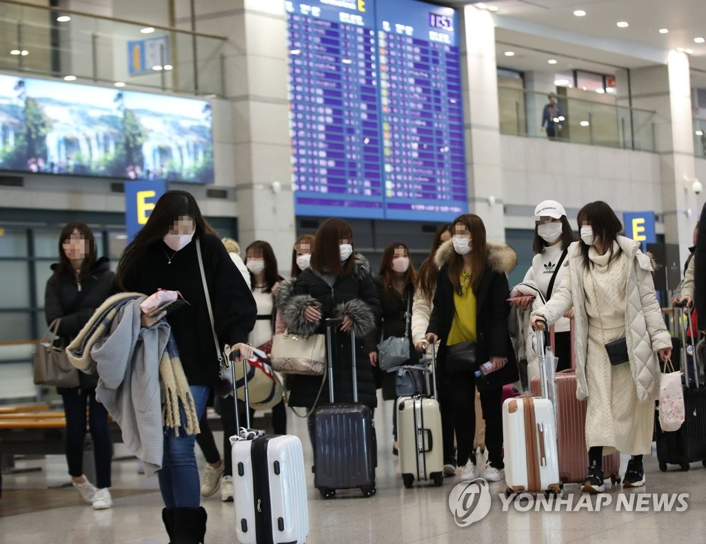 This photo taken on Feb. 16, 2020, shows people with masks at Incheon International Airport, west of Seoul. (Yonhap)