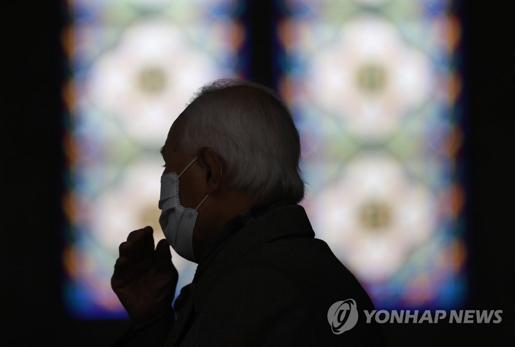 A Catholic believer wears a mask in Myeongdong Cathedral in Seoul on Feb. 26, 2020. (Yonhap)