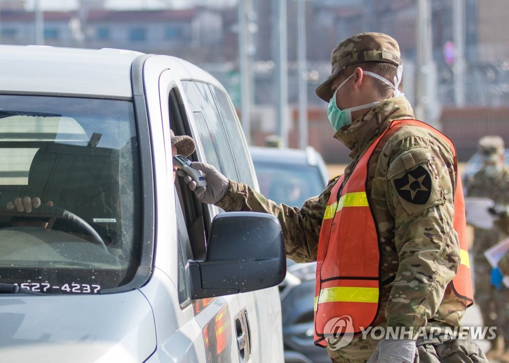 In this February file photo provided by United States Forces Korea, a military guard at U.S. Army Garrison Humphreys in Pyeongtaek, 70 kilometers south of Seoul, checks the temperature of a driver to screen entrants to the compound for the novel coronavirus. (PHOTO NOT FOR SALE) (Yonhap)
