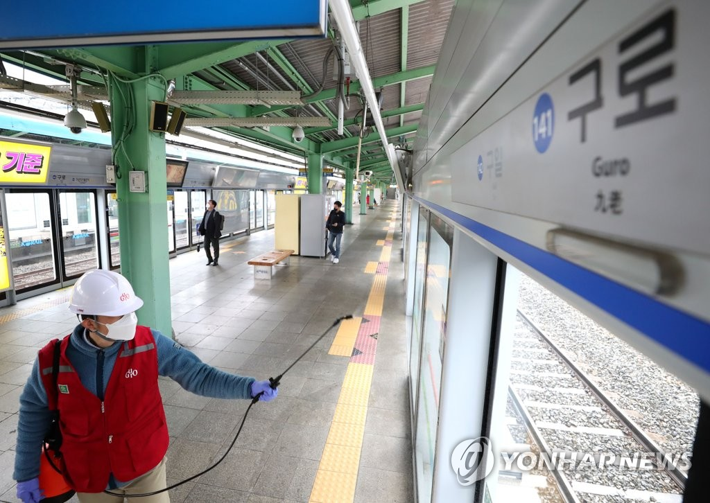 A city official disinfects Guro subway station in southwestern Seoul on March 10, 2020, after a patient who worked at a nearby building was found to have visited the station. (Yonhap)