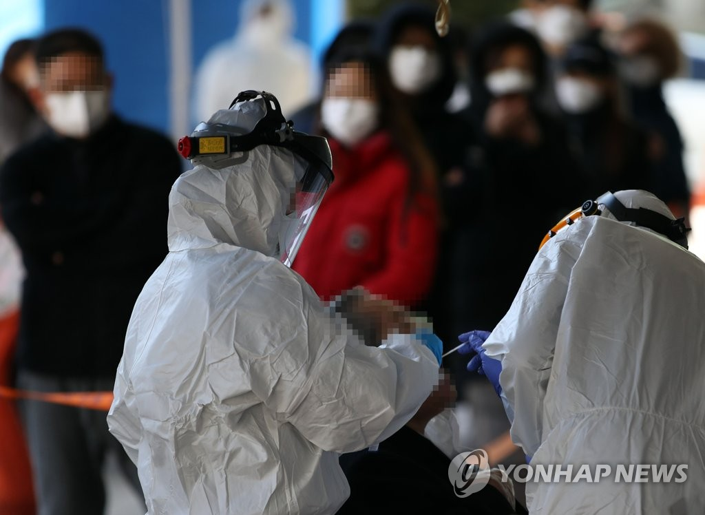 Health officials examine residents at a virus screening center set up on the first floor of a building in southwestern Seoul on March 11, 2020. (Yonhap)