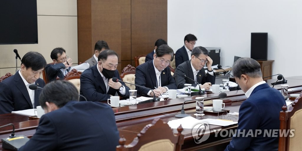 President Moon Jae-in (front, R) receives an emergency briefing from Finance Minister Hong Nam-ki, wearing a face mask, and Bank of Korea Gov. Lee Ju-yeol (back, L) at Cheong Wa Dae on March 13, 2020. (Yonhap)