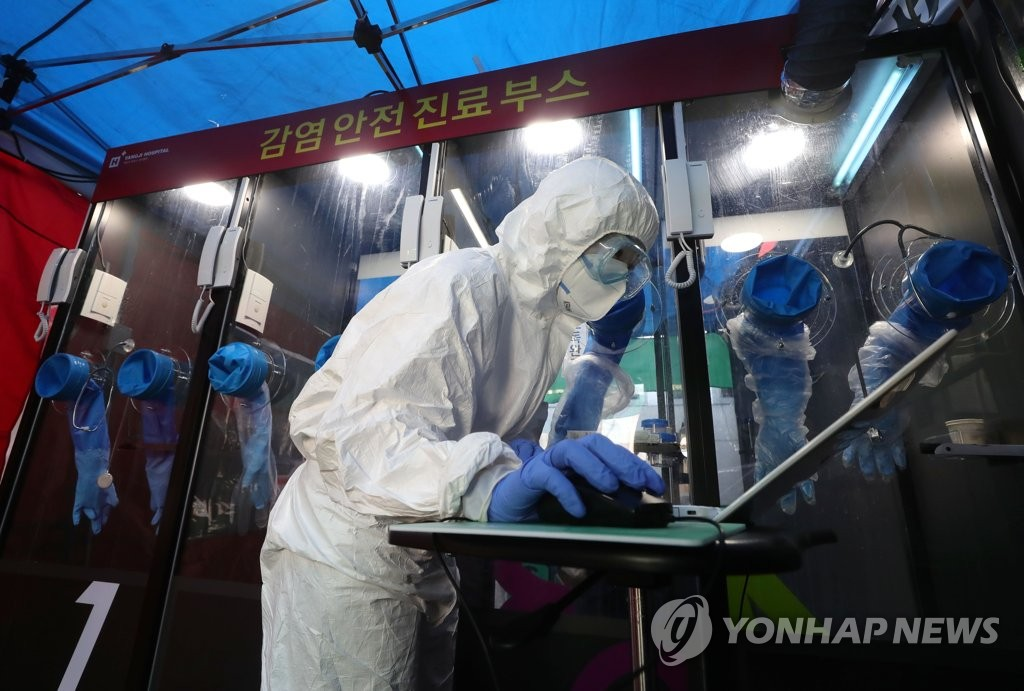 A health worker conducts virus tests at H Plus Yangji Hospital in Seoul on March 16, 2020. (Yonhap)