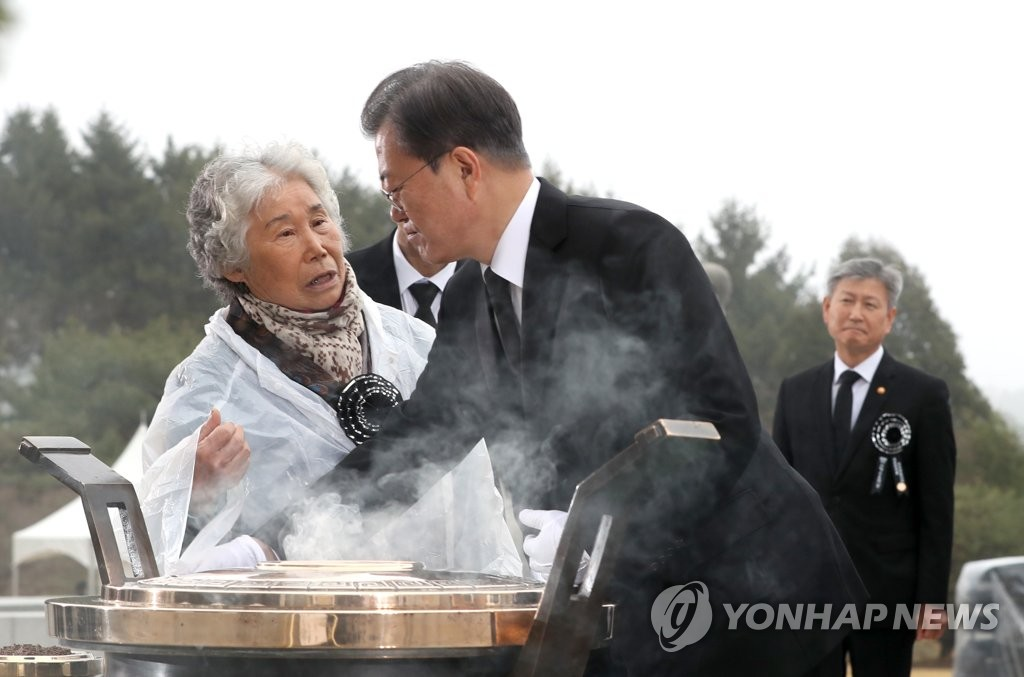 The mother of a Cheonan warship sinking victim speaks to President Moon Jae-in while he was burning incense at the Daejeon National Cemetery on March 27, 2020. (Yonhap)