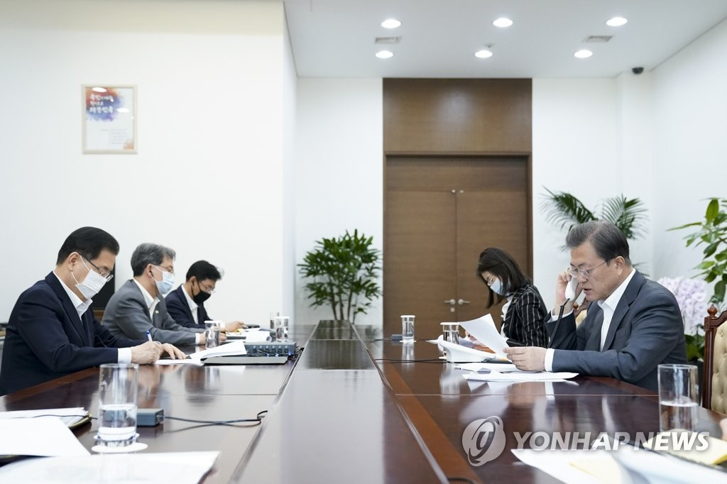South Korean President Moon Jae-in (R) speaks by phone with World Health Organization Director-General Tedros Adhanom Ghebreyesus at Cheong Wa Dae in Seoul, with his aides listening in, in this photo provided by Moon's office on April 6, 2020. (PHOTO NOT FOR SALE) (Yonhap)