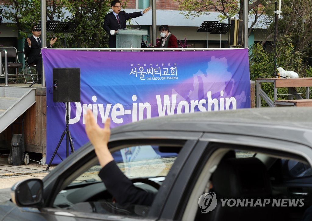 Members of Seoul City Church in the eastern Seoul ward of Jungnang take part in a drivethru Sunday service in a parking lot on April 19, 2020. (Yonhap)