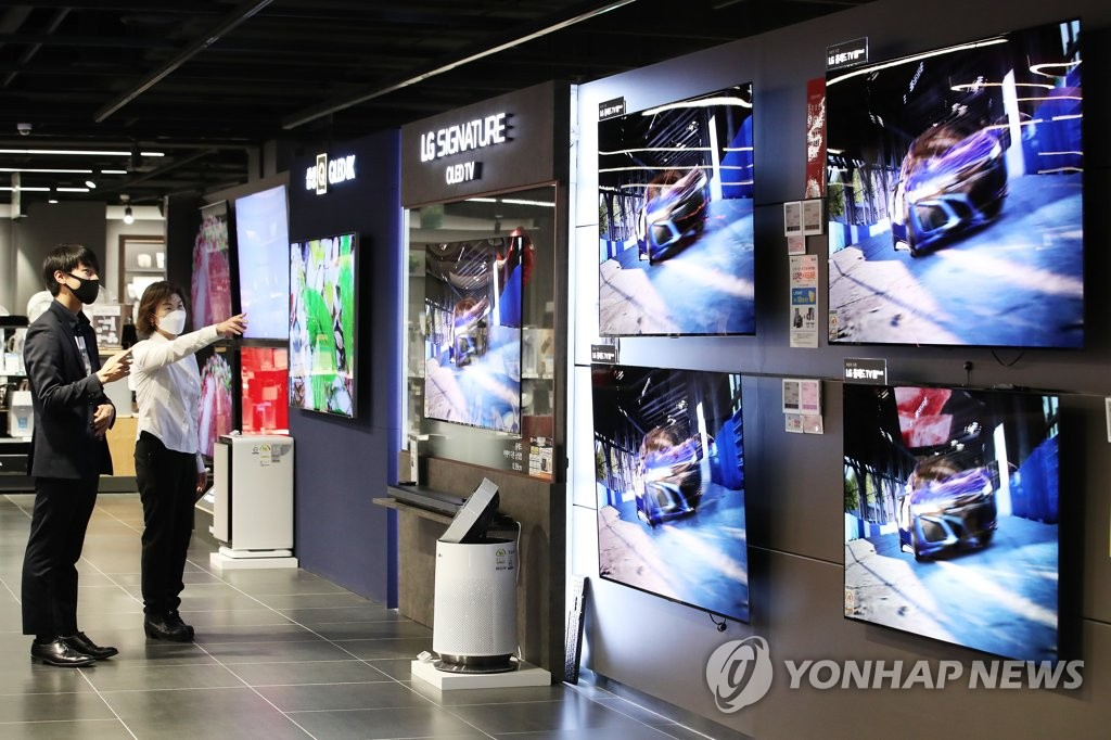 This file photo, taken on April 29, 2020, shows customers looking at TVs at a store in Seoul. (Yonhap)
