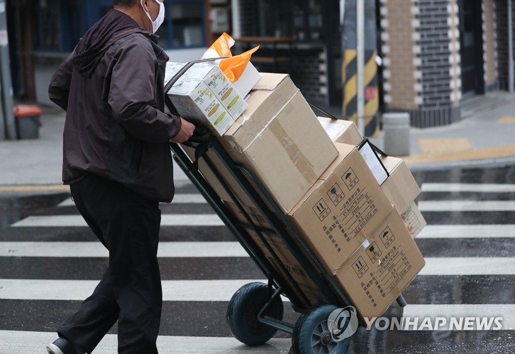 A deliveryman moves boxes in Jongno, central Seoul, on May 1, 2020. (Yonhap)