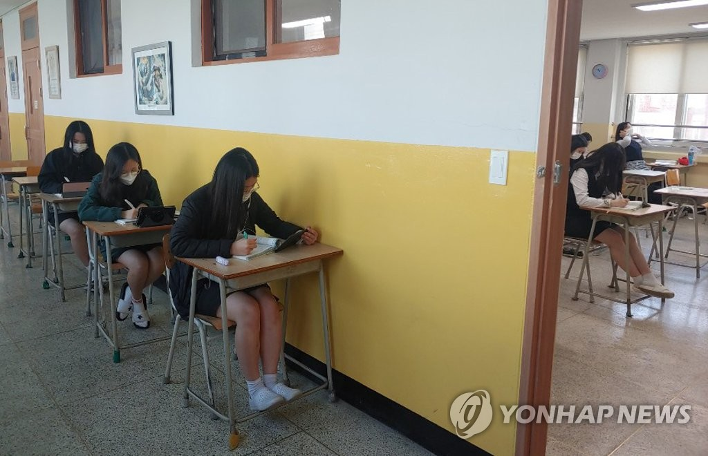 Some students take a class in the corridor of a high school in Cheongju, 137 kilometers south of Seoul, on May 20, 2020, by using tablets as the class was streamed at the same time, in this photo provided by a Yonhap reader. (PHOTO NOT FOR SALE) (Yonhap)