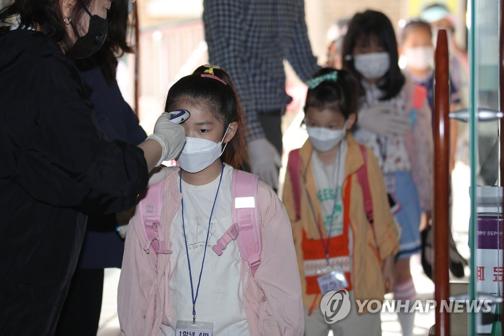 Students have their body temperatures checked at an elementary school located in Gwangju, 330 kilometers south of Seoul, on May 27, 2020. (Yonhap)