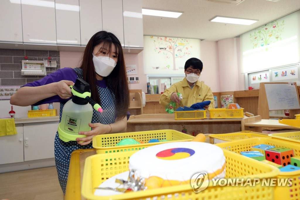 A teacher and a government official disinfect toys and teaching materials at a child care center in Gwangju, 329 kilometers southwest of Seoul, on June 1, 2020, following the suspension of its operation over the new coronavirus. (Yonhap)
