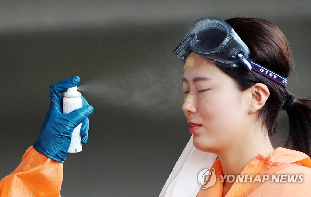 A medical worker gets her face cooled with a facial mist at a makeshift clinic in Gwangju, 330 kilometers south of Seoul, on June 5, 2020. (Yonhap)
