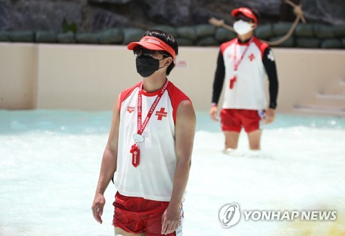 Water park lifeguards wear masks