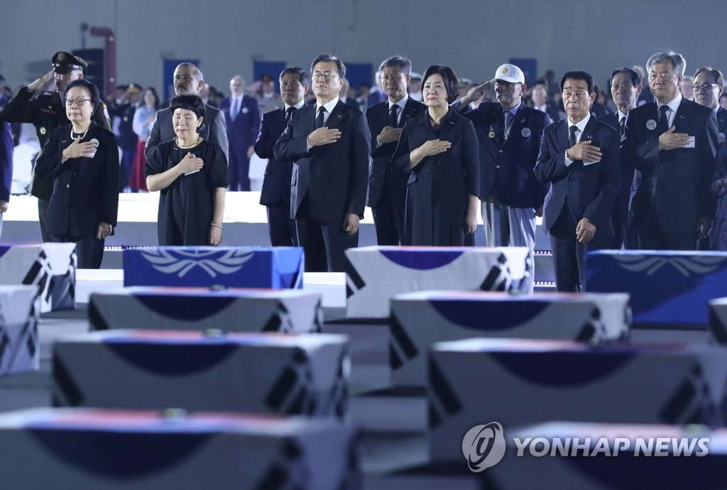 President Moon Jae-in (3rd from L, front) salutes to the national flag in front of flag-draped boxes of repatriated war dead remains at Seoul Air Base, just southeast of Seoul, on June 25, 2020. (Yonhap)
