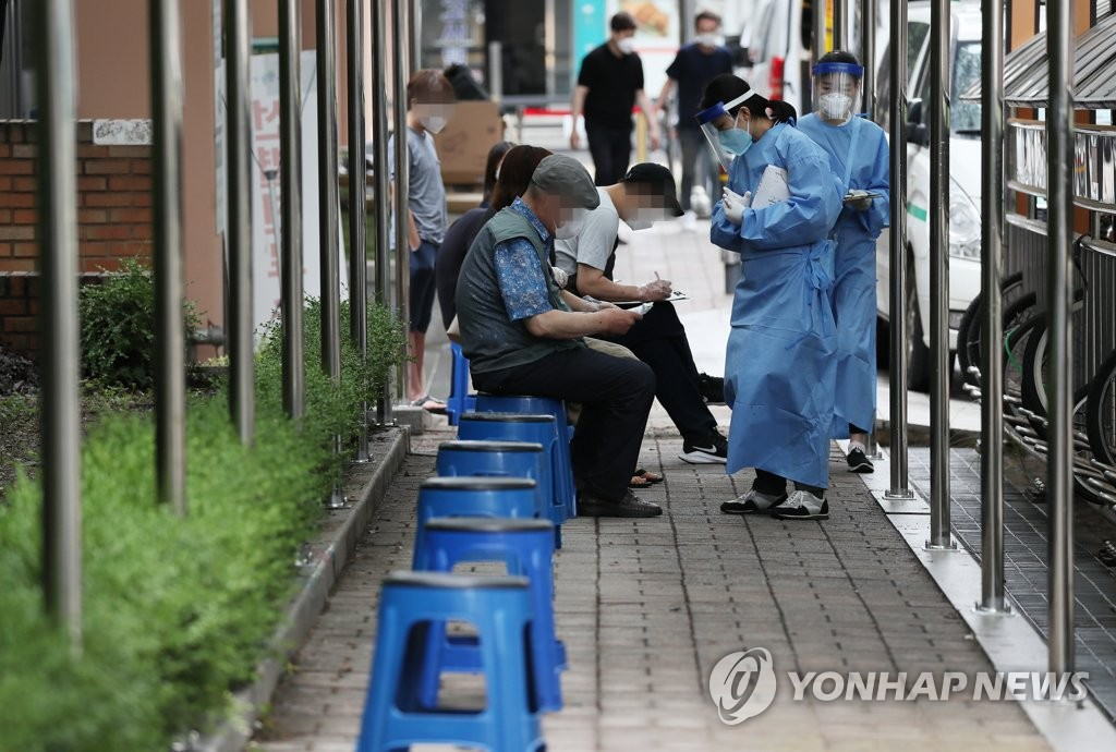 Citizens wait to receive new coronavirus tests at a screening site in Seoul's southwestern ward of Gwanak on June 30, 2020. (Yonhap)