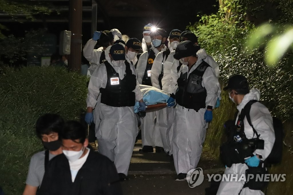 Police carry the body of Seoul Mayor Park Won-soon, who was found dead in the forested hills of Mount Bugak in Seoul on July 10, 2020. (Yonhap)