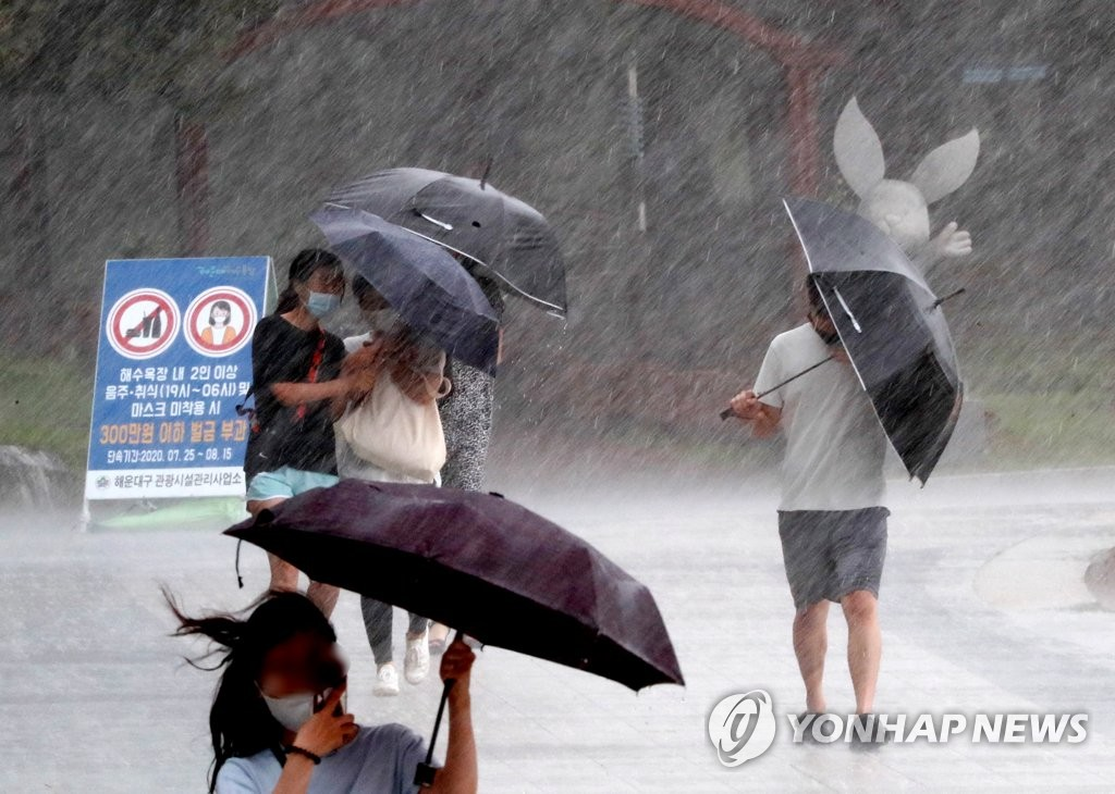 Pedestrians struggle to hold onto their umbrellas as heavy rain, accompanied by strong winds, poured in the southeastern port city of Busan on Aug. 10, 2020. (Yonhap)