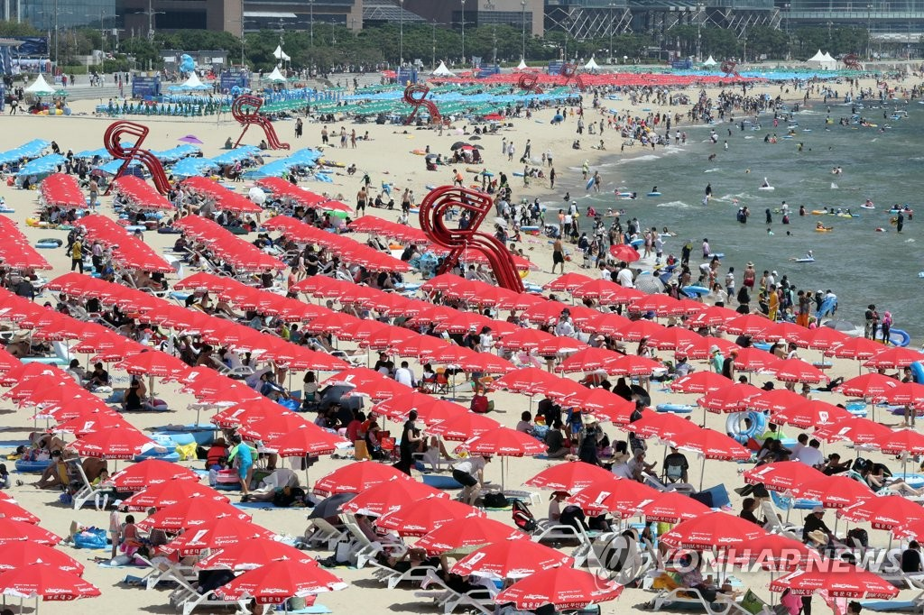 People relax at Haeundae Beach in the southeastern port city of Busan on Aug. 16, 2020. (Yonhap)