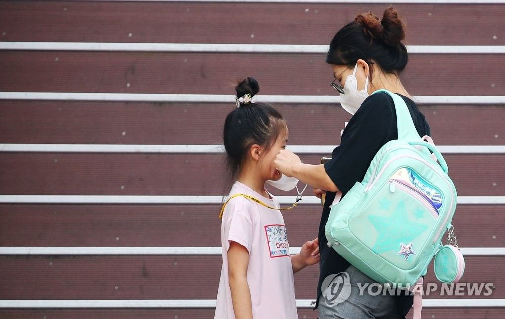 A mother helps her child put on a mask near an elementary school in western Seoul on Aug. 25, 2020. (Yonhap)