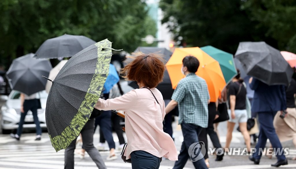 People walk with umbrellas during their morning commute in Yeouido, a business district in western Seoul, on Aug. 27, 2020. (Yonhap)