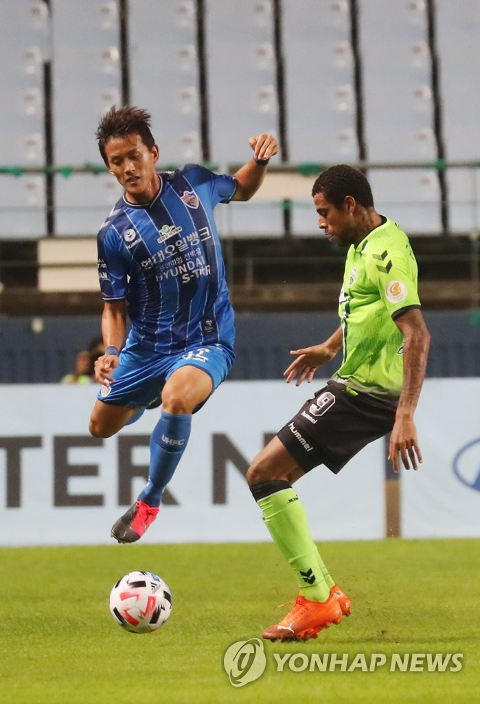 Hong Chul of Ulsan Hyundai FC (L) and Gustavo of Jeonbuk Hyundai Motors battle for the ball during a K League 1 match at Jeonju World Cup Stadium in Jeonju, 240 kilometers south of Seoul, on Sept. 15, 2020. (Yonhap)