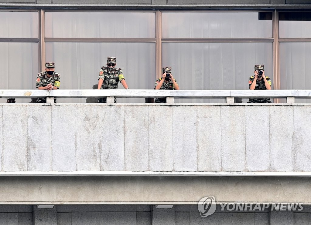North Korean soldiers watch visiting South Korean Unification Minister Lee In-young through a telescope from the North Korean side of the inter-Korean truce village of Panmunjom in Paju, north of Seoul, on Sept. 16, 2020. (Pool photo) (Yonhap)