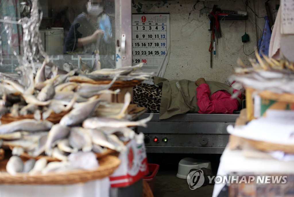 A merchant takes a break at a marketplace in central Seoul as few customers visited the shop amid the new coronavirus pandemic on Sept. 21, 2020. (Yonhap)
