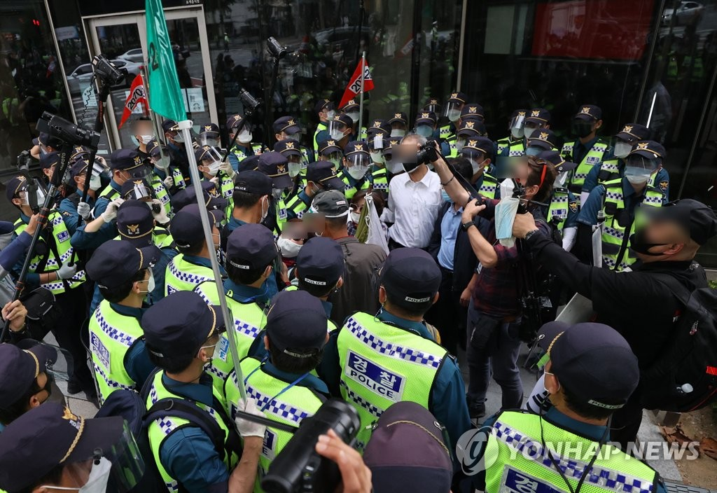Police officers break up a group of activists trying to hold a rally near the Jongno Ward Office in central Seoul on Oct. 3, 2020. (Yonhap)