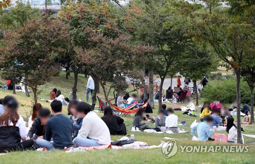 This photo shows people visiting a Han River park in Yeouido, Seoul, on Oct. 11, 2020, as the government relaxed social distancing guidelines to the lowest tier of Level 1. (Yonhap)